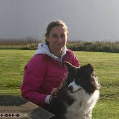 Alison Roets with her Border Collie Freya sitting at the picnic table, Landsend, Cornwall