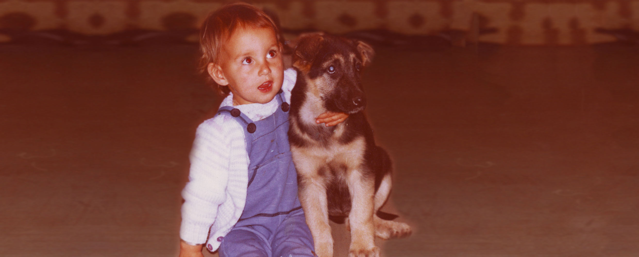 Alison Roets as a toddler with Tarka the German Shepherd