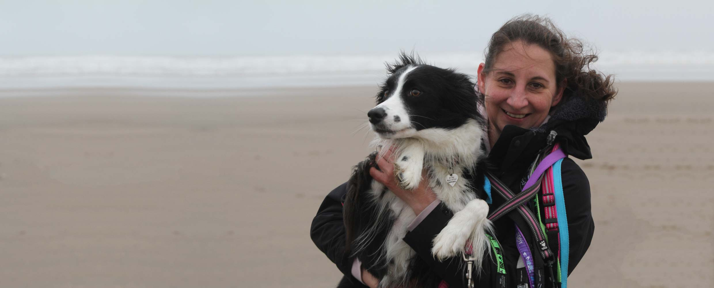 Alison Roets of Freyasway holding Muse the Border Collie on the beach