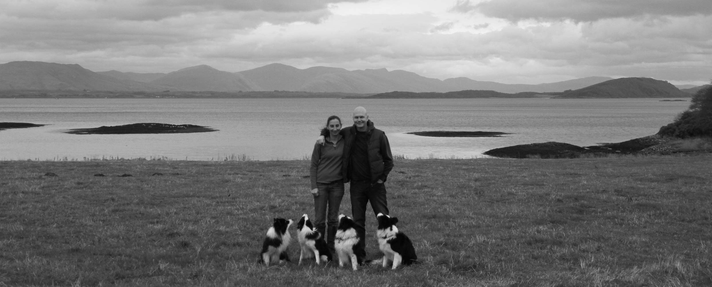 Alison Roets and Rob Evans with their Border Collies, Oban beach, Scotland